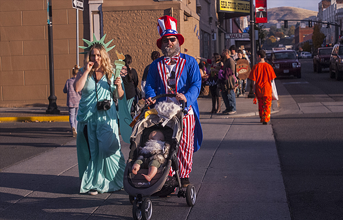 Nic (Uncle Sam) and Lindsay (Statue of Liberty) Jenkins with their nine-month old-son Maverick as they cross Federal Street heading west on Second.
