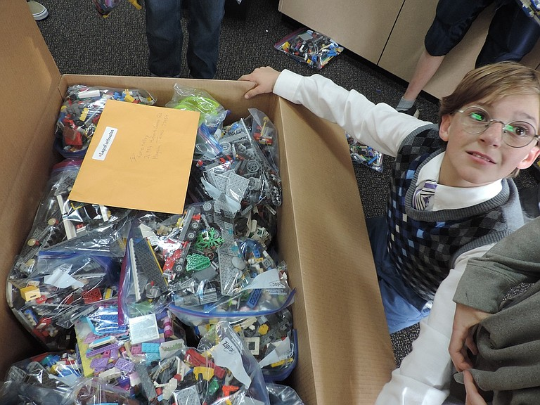 LEGOS to go: Johnny Irvine with some of the Legos the robotics clubs collected this fall for kids in Houston.