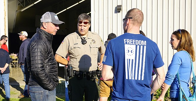 Ryan Hartman, Insitu CEO, left, and others talk with Hood River County Sheriff Matt English at Insitu's fire responder appreciation event Oct. 28 at Hood River County Fairgrounds.