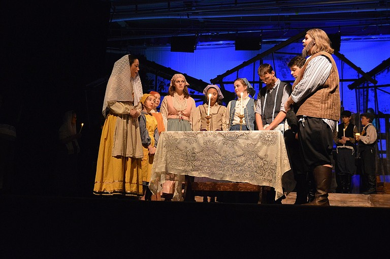 Tevye, right, played by Aiden Tappert, and Golde, left, played by JoJo Summersett, celebrate the Sabbath with their children and guests: Bielke (Abriela Lopez), Shprintze (Lucy Hager), Chava (Katelyn McAllister), Hodel (Lily Galvez), Tzeitel (Lauren Church), Motel (Onar Smith) and Perchik (Cooper Case).