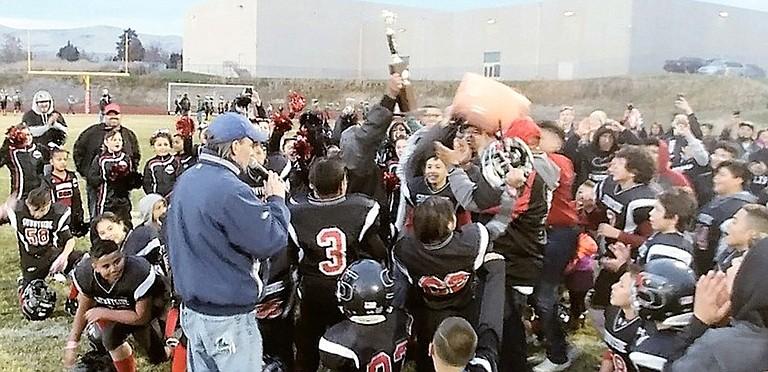 The Sunnyside B-Black team celebrates winning the Grid Kid championship trophy Saturday.