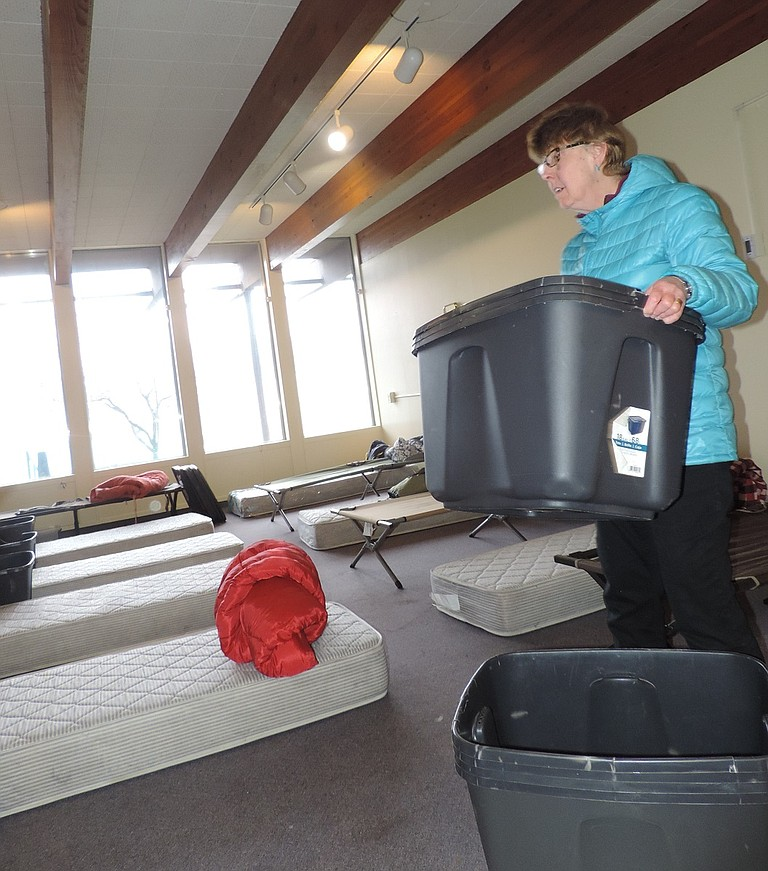 VOLUNTEER Fran Finney sets up cots, sleeping bags and tubs for guests' belongings in a room at Riverside Church.