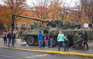 A class at The Dalles Middle School checks out a Stryker assault vehicle prior to an assembly to honor veterans Thursday morning. The armored eight-wheeled Stryker is based at the Fort Dalles Readiness Center. Students were able to look into its hatches and learn that the vehicle is operated by a team of three soldiers.