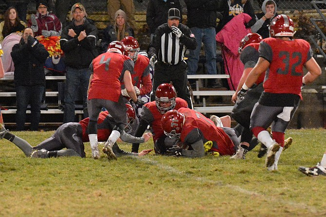 Dalton Swayze (71) of Okanogan jumps on a Naches Valley fumble in the first quarter of a state 1A first-round game Friday, Nov. 10, at Okanogan.