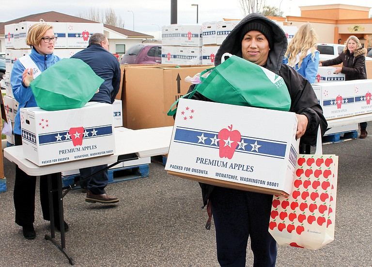 Rosa Chavez of Toppenish carries a box of food, including a 20-pound turkey, to her car. She was one of those who braved the cold Monday to take home one of the 250 turkeys handed out  by the Second Harvest event. Also pictured is Yakima Valley Co-Dairy Ambassador Cobi Van Slageren, one of the many volunteers on site to help.