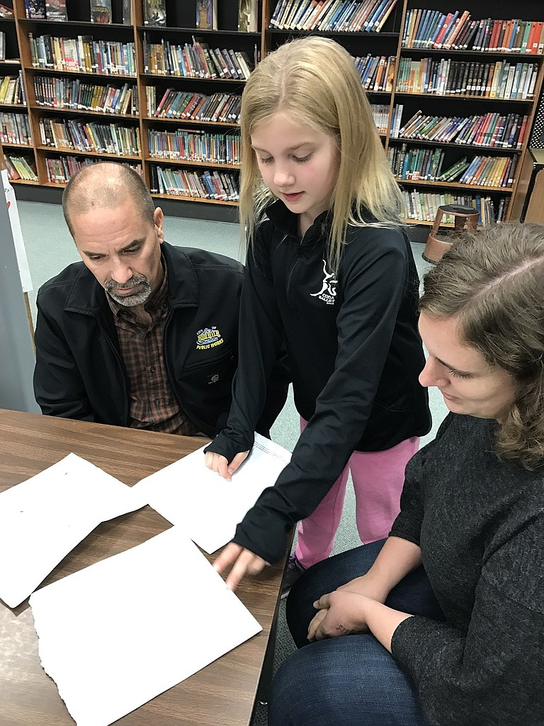 FIFTH grader Hailey Harjo of Westside Elementary shows her design and those of two classmates to City Public Works Director Mark Lago and Council Member Megan Saunders during the interview visit to the school by consultant Lisa DeShano, who sat in the library and took down numerous ideas from students, below.
