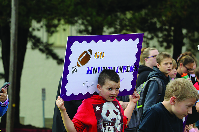A young fan holds up a sign to cheer on the Mountaineers on Friday.