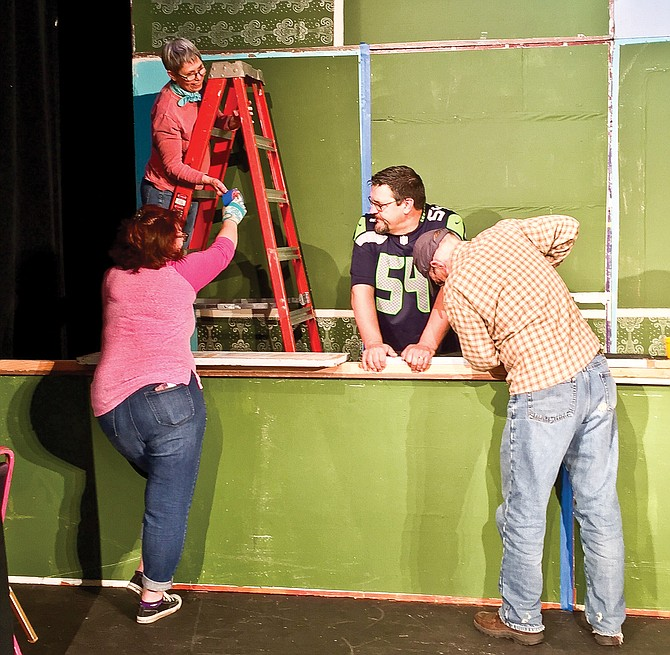 """Set construction is underway for Valley Theater Company's Christmas plays, """"A Charlie Brown Christmas"""" and """"Christmas Every Day."""" From left, Julie Funfar, Sheryl Cole (on ladder), Rick James and Steve Cole work on the set at Prosser's Princess Theatre."""