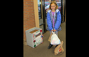 Evelyn Rogers, a third grader at St. Mary's Academy, drops off her donations for the Holiday for Heroes Committee.