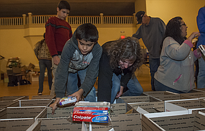 A host of volunteers packed care packages for the troops Thursday evening at the Civic. Pictured, Joseph and his mom Nancy Lutz add items to boxes as her son Trevor stands ready to help.