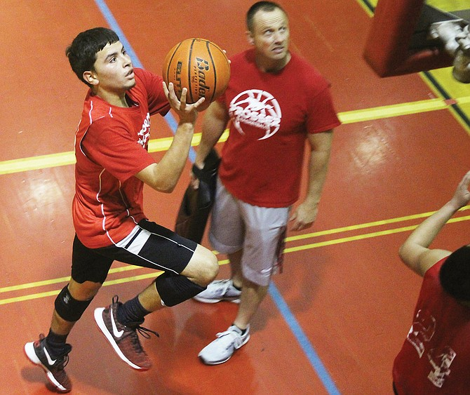 Sophomore Lisandro Santillan goes up for a layup during practice last night as coach Toby Cox watches. The Mustangs open their season with a jamboree at Mabton this weekend, then move on to regular play against Granger on Dec. 1. League play begins Dec. 2 at East Valley (Yakima).