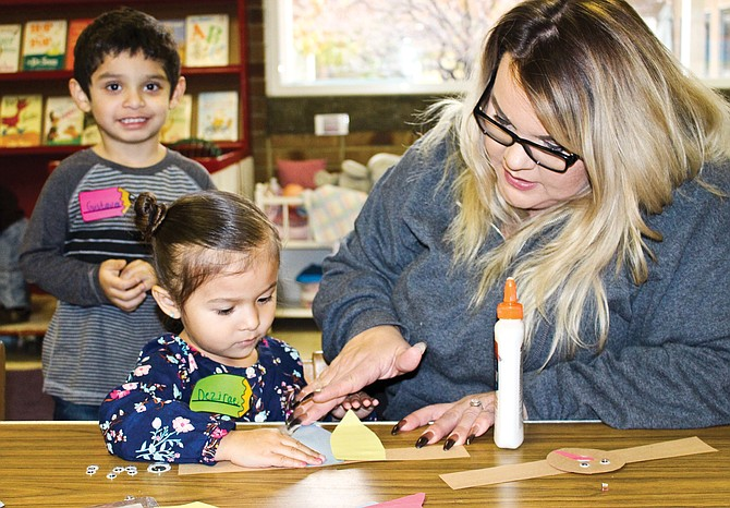 Dezirae Galvez, 3, carefully glues paper feathers to her headband with the help of Breezi Campos during pre-Thanksgiving craft time at Sunnyside Preschool on Tuesday as Gustavo Davila, 4, looks on from behind.
