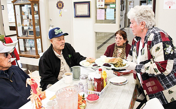 Grandview Senior Center volunteer Wanda Brewer, right, serves a traditional turkey dinner to Manuel Garcia Pena and Eva Benitez Flores at the annual Thanksgiving party and dinner Wednesday.