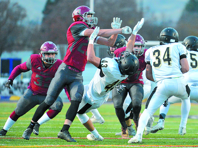 Levi Veenhuizen (23) of Okanogan tries to get to a Royal runner while leveling the Knights' Jack Diaz (43). At left is Colton Sam (32) of Okanogan.