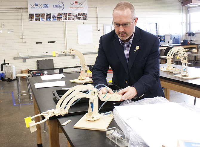 Tim Ray, Dallas High School's career and technical education coordinator, demonstrates a hydraulic crane that engineering students built earlier in the school year.