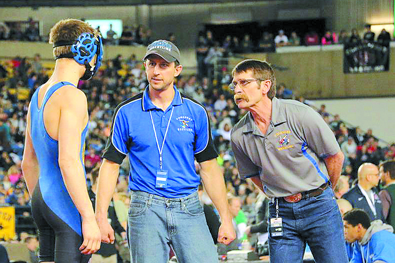 A Tonasket wrestler gets instructions at last year's state tournament in the Tacoma Dome. Dave Mitchell, who retired after 39 years, is at right. At center is incoming coach Cole Denison.