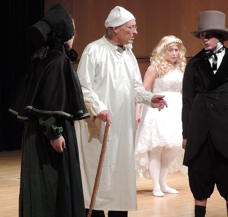 "SCROOGE transformed: As a young man (Max Meckoll) is spurned by his fiancé, Belle (Elena Lundby) who sees in his heart ""the master-passion, Gain."" Looking on unseen are Scrooge and the Ghost of Christmas Past (Maren Euwer)."
