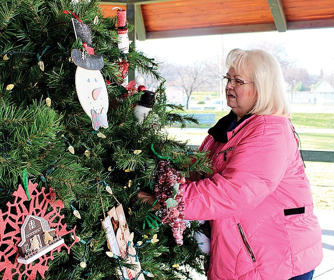 Sunnyside Arts Commission chair Kathleen Rogers oversees the decorating of the Centennial Square Christmas Tree, which will be lit at 6:30 p.m. as part of the kick-off to the Lighted Farm Implement Parade weekend.  Arts commissioners and volunteers from Tom Dolan's YV-Tech Welding class helped with decorating of the square.