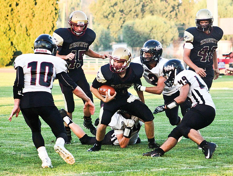 Knights quarterback Chance Marsh maneuvers his way past Almira-Coulee-Hartline's defense during this season's opener Aug. 31. Kyler Marsh and Cade Bosma are in the background.
