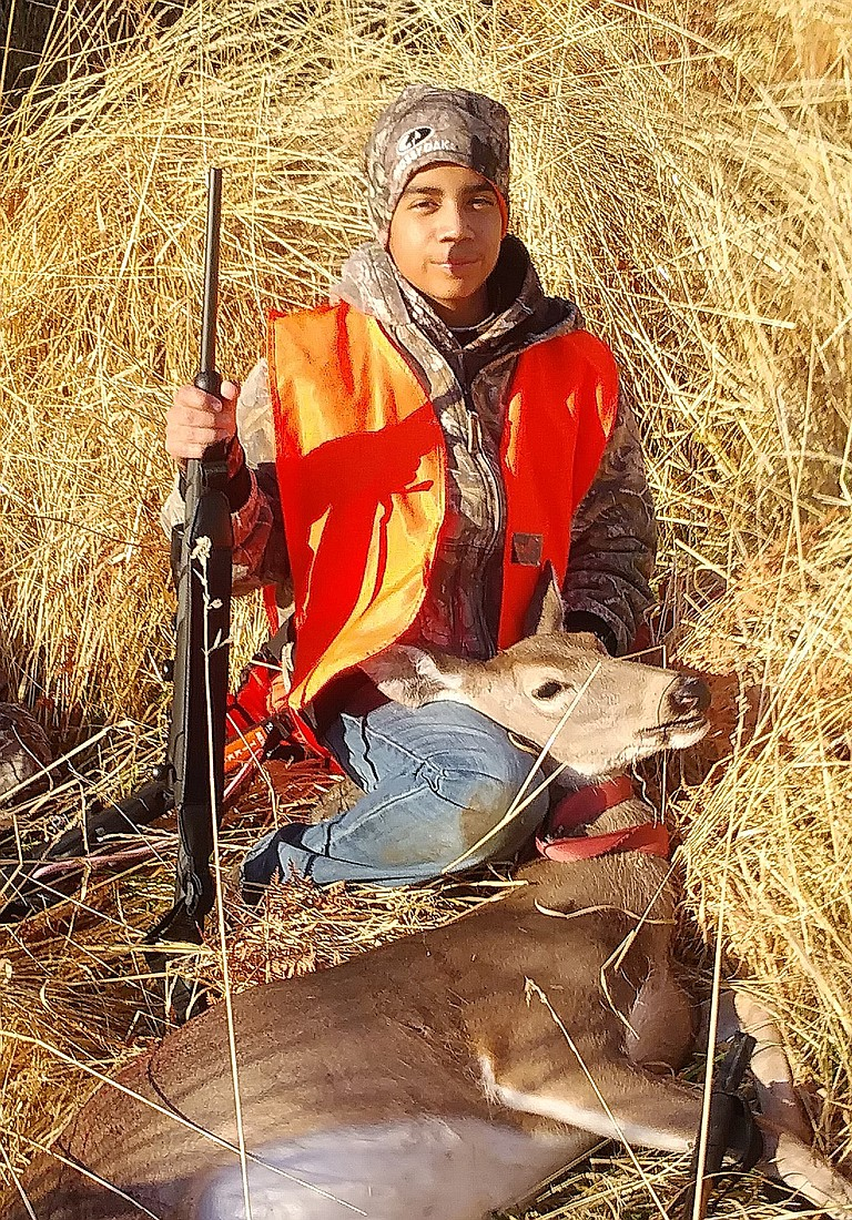 13-year-old Angel Tovar of Mabton, son of Angel and Maria Tovar, sits with a whitetail doe he shot on the opening day of modern firearm season outside Waitsburg at 130 yards. Tovar has been hunting three years and was with his father, uncle Jaime Tovar and cousin Jaime Tovar of Grandview.