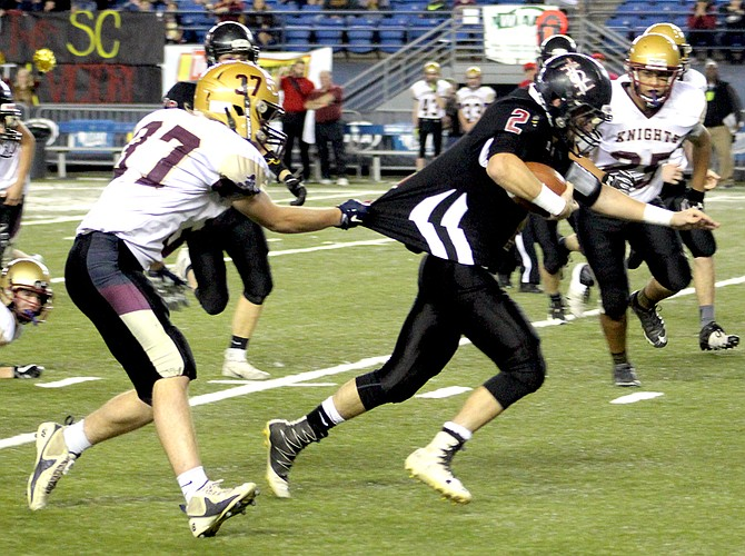 Sunnyside Christian junior outside linebacker Lucas Dykstra gets a hand full of jersey as Warrior Parker Zappone races upfield in Friday's state 1B football championship game in the Tacoma Dome.