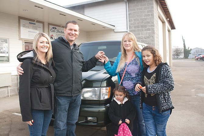Trina Wright and Rick Young present Christina Smith and her two daughters, Bella Allen, 3, and Gracee Allen, 10, the keys to a 2000 Isuzu Trooper.
