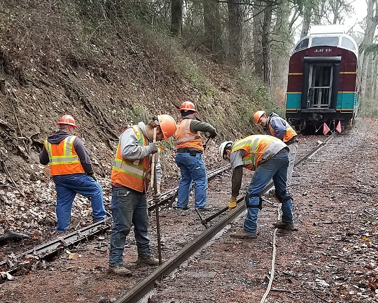 Saturday's Mt. Hood Railroad crew repairs the track after a derailment canceled trains Friday night.