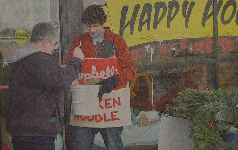 December 5, 2007: At Rosauers, HRVHS senior Zach Flaming, dressed in a foam rubber soup costume, thanks Connie Rose of Parkdale for her donation to the can food drive organized by high school students. Cash donations are redeemed at six cans per dollar. For the next two weeks, students will be making the rounds, seeking food and cash gifts for the campaign, with all proceeds going to FISH Food Bank and Christmas Project. Photo by Kirby Neumann-Rea.
