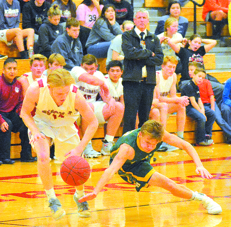 Kolby Picard of Okanogan and Owen Hevly of Liberty Bell attempt to run down a loose ball.