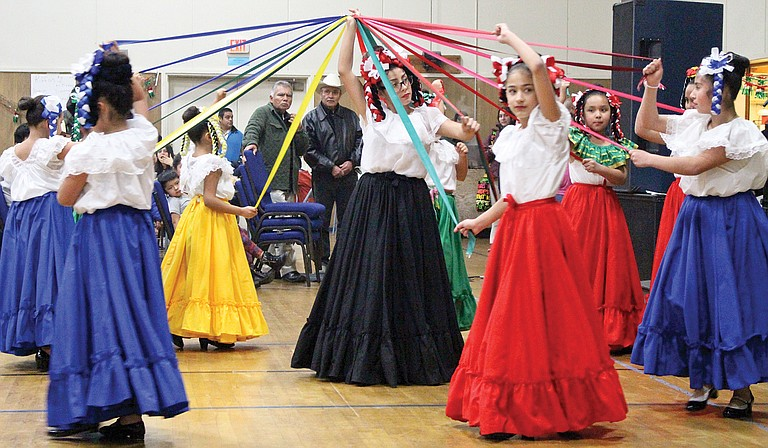 Panda Bear Child Care Center dancer Jazmine Gonzalez stands in the center of the ribbon dance as her fellow dancers pay tribute to the Virgin of Guadalupe Tuesday at St. Joseph's Catholic Church Parish Center.