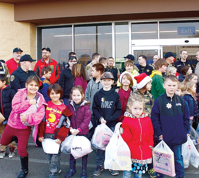 Children from Falls City and Grand Ronde get ready to pose for a group photo with Polk County Sheriff's deputies and Grand Ronde Tribal Police officers on Saturday at the Dallas Walmart. The annual Shop with the Sheriff event purchased gifts for 32 children.