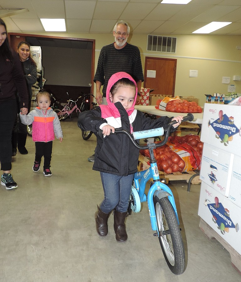 NAVAEH Badillo, 5, of Hood River tries out a bicycle she received along with other gifts and food Friday at Christmas Project. Volunteer Mark Zanmiller gave her some steering lessons. She was there with her mother, Yaneli, aunt Julie, and her sister,Aaliyah, 3.A fundraising letter this fall highlighting the bike program helped reap $15,000 in donations.