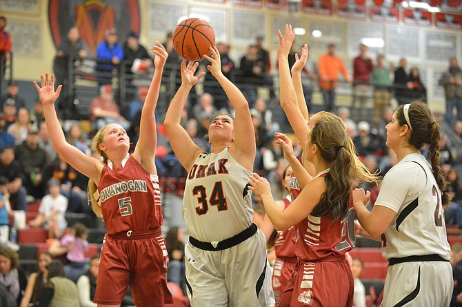 Jamie Utt (34) of Omak and Paxton Wood (5) of Okanogan go for a rebound.