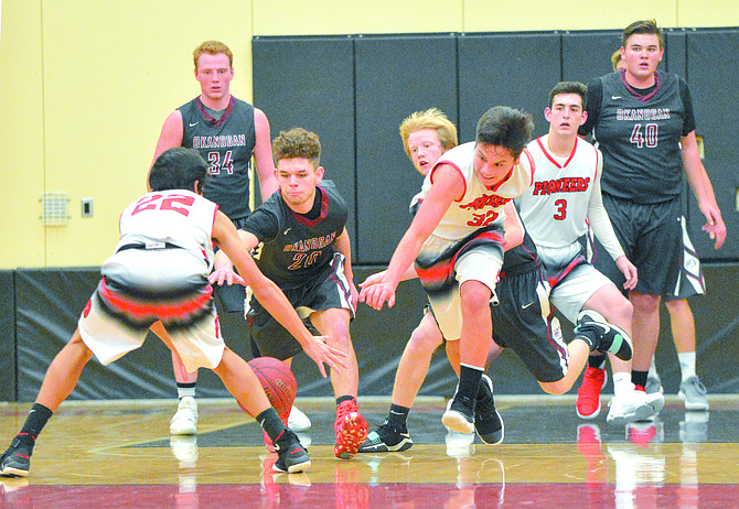 Martin Grooms (20) of Okanogan reaches for a loose ball, as do Omak's JoJo Ibarra (22) and Tre' Marchand (32).