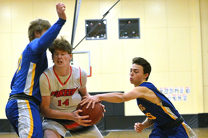Kanen Ables of Omak, center, is surrounded by Tonasket defenders Ryker Ayers (22), left, and Jordan Thrasher (10).