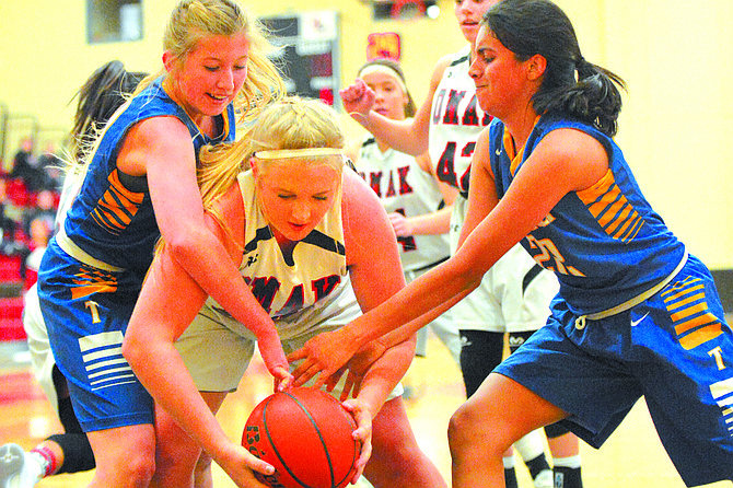 Kelsey Vejraska of Omak (center) fights to keep the ball away from Tonasket's Karlie Richey (left) and Kaylee Bobadilla.