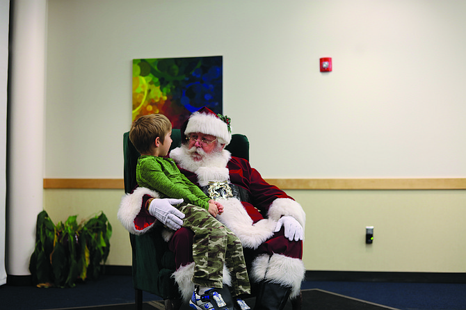 Santa Claus listens carefully to the wish of a little boy at the Monmouth Christmas Tree lighting. He will be busy this week in the countdown to Christmas — just five days away.