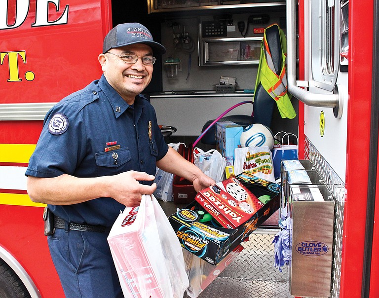 Sunnyside Fire Department captain Tony Castillo picks up donated of toys and clothes at the Nouvella Club Christmas tea Thursday. He said the toys would glad the hearts of five local families.