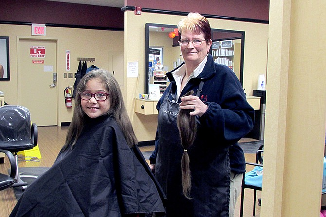Aliya Rodriguez is all smiles as hairstylist Denise Schulz holds up the 17 inches of hair Rodriguez will be donating to Wigs For Kids.