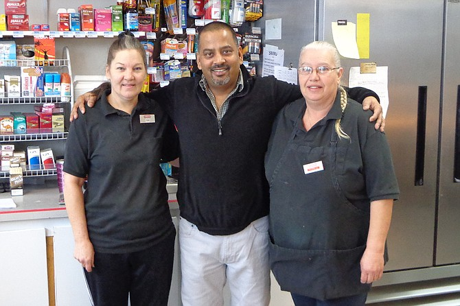Cashier Tina Levi, new owner Herman Kataria and manager Debbie Wieland pose for a photograph at the Conoco convenience store at 414 Hanford St.