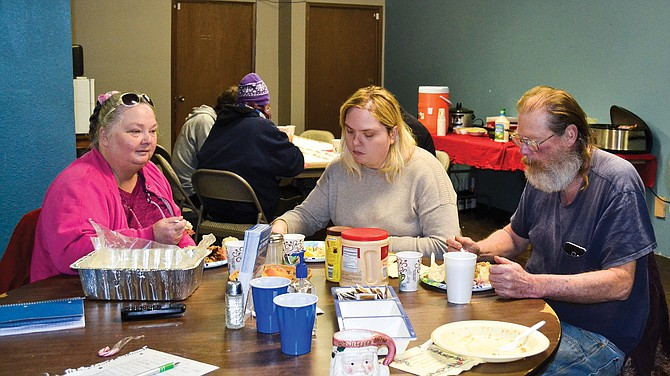 The homeless in Sunnyside may not have a place to stay, but they have a place to go every year at his time, the Christmas dinner Elizabeth Knowles prepares and serves at the Underground. Three enjoy their meal together.