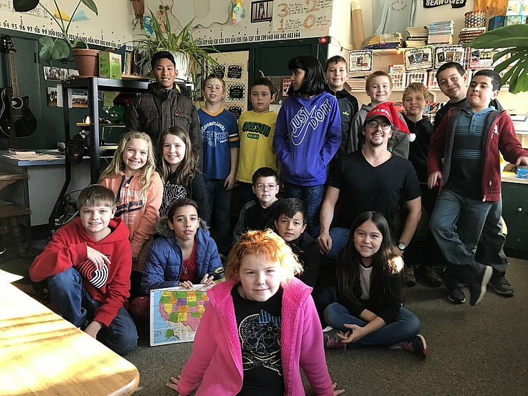 CASCADE LOCKS fourth and fifth-graders, and teacher Derek Gries, pose with Trinity Evans, front. Many of these students have shared a classroom as far back as pre-school days.