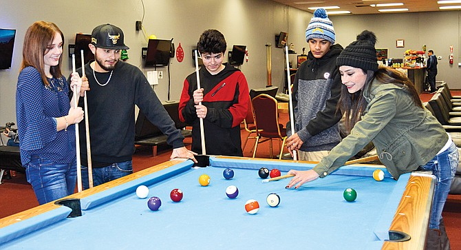 These young members of the Villalobos clan of Sunnyside sharpen up their pool skills at the Turtle Lounge in Sunnyside in preparation for the long New Year's Eve night planned at the business that caters to minors.