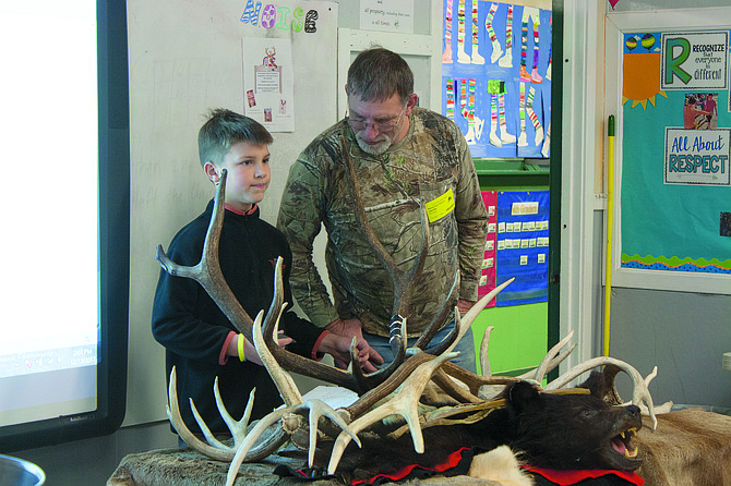 Christopher Younk, left, and his father, Michael Younk, shared photos, antlers and stories from his hunting excursions with his schoolmates.