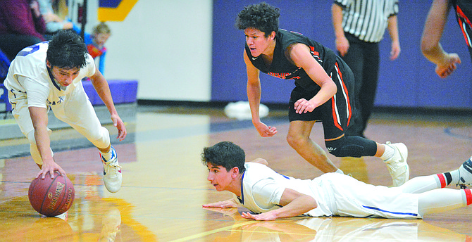 Andrew Gonzalez of Pateros grabs a loose ball during Dec. 28 game in Pateros. At right are Ivan Ceniceros of Pateros and Ronaldo Ubaldo of Bridgeport.