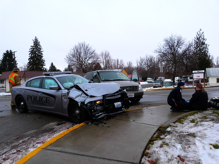 An Omak Police Department car and a minivan are damaged in accident.