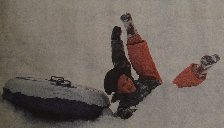 January 14, 1998: Christy Thomson looks like she fell head-over-heels in love with the storm Sunday as she sleds down 12th Street. Photo by Keith Fredrickson.