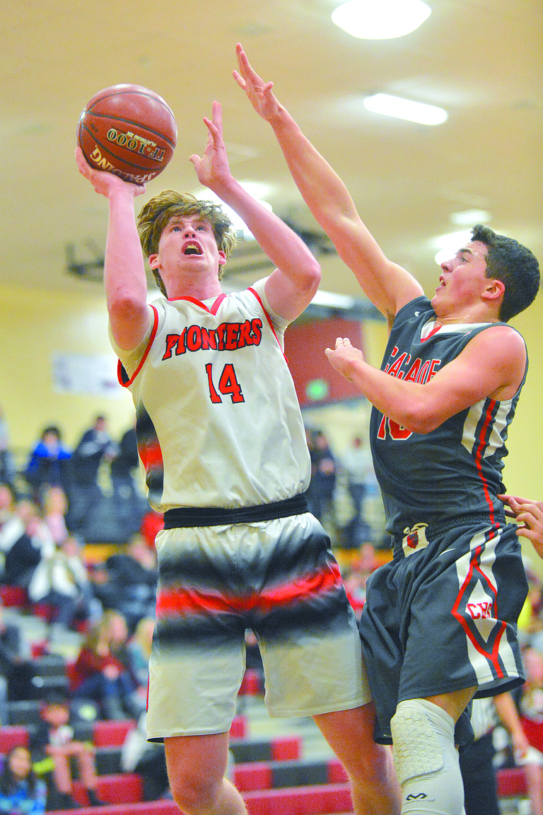 Kanen Ables of Omak goes up for a shot against Isaac Cortes of Cascade on Jan. 5.