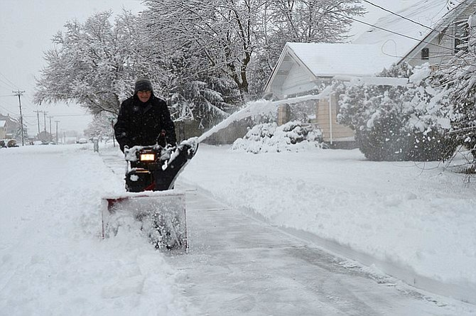 Kirk Silves clears a path along the sidewalk near his home on North Fourth Avenue, Okanogan.