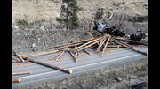 Crews with the Idaho Department of Transportation clear the roadway of logs spilled during an early Monday evening logging truck rollover accident, Jan. 27, at the north entrance to Pollock on U.S. Highway 95.